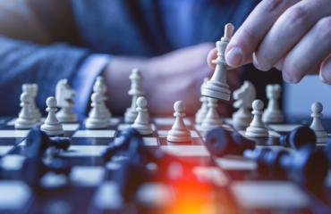 hand holding chess piece - becoming a new era pharmacy webinar