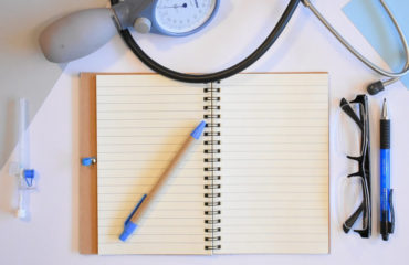 medical billing - notebook on desk with stethoscope and blood pressure cuff