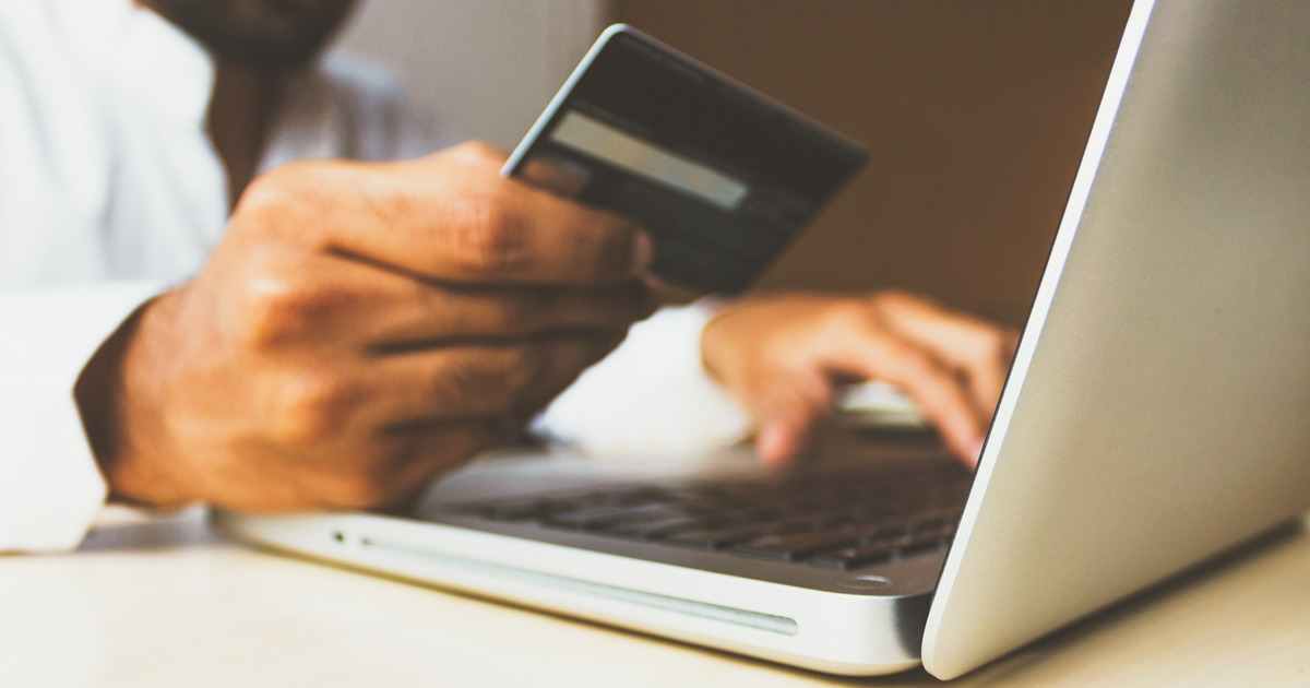 pharmacy claims - man using credit card with laptop