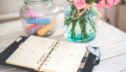 day planner on table with flowers - year in review webinar